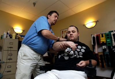 In this photo taken Dec. 13, 2010, quadriplegic Adam Martin, right, works with physical therapist Wes Bower at the Sarasota Health and Rehabilitation Center, the nursing home where he lives.