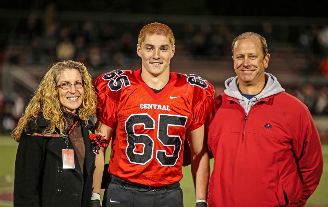 """(Patrick Carns via AP) This Oct. 31, 2014, photo provided by Patrick Carns shows Timothy Piazza, center, with his parents Evelyn Piazza, left, and James Piazza, right, during Hunterdon Central Regional High School football's """"Senior Night"""" at the high sch"""