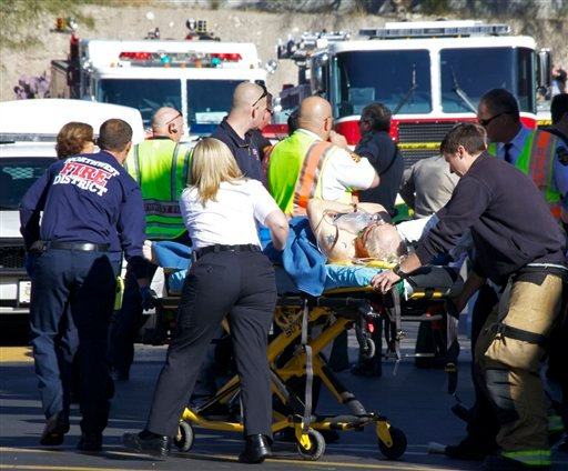 Emergency personnel attend to a shooting victim outside a shopping center in Tucson, Ariz. on Saturday, Jan. 8, 2011 where U.S. Rep. Gabrielle Giffords, D-Ariz., and others were shot as the congresswoman was meeting with constituents. (AP Photo)