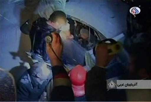 In this image made from TV rescue workers attend the scene after an IranAir passenger jet carrying around 100 people crashed as it was making an emergency landing Sunday Jan 9 2011. (AP Photo / Al Alam)