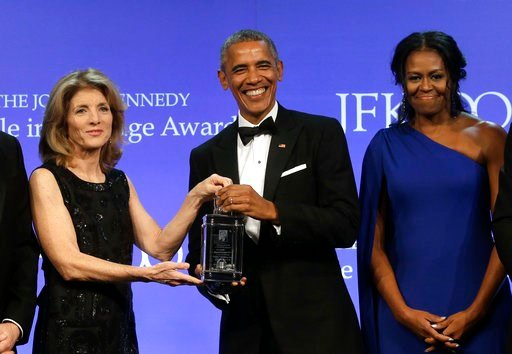 Former President Barack Obama is presented with the 2017 Profile in Courage award by former U.S. Ambassador to Japan Caroline Kennedy, as former first lady Michelle Obama looks on May 7, 2017, in Boston. (AP Photo/Steven Senne)