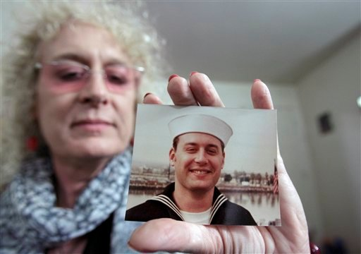 Autumn Sandeen holds a November, 1980 picture of herself as a man and navy seaman recruit Tuesday, Nov. 23, 2010, in San Diego. (AP Photo/Gregory Bull)