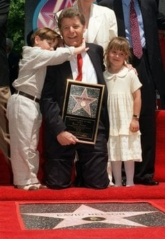 FILE - This file photo taken May 9, 1996, on the Hollywood Walk of Fame in Los Angeles actor and director David Nelson poses with his grandson Michael Woolery and family friend Ashley Holt as he is honored with the 2,065th star.