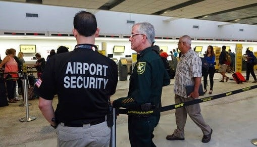Airport Security and a Broward Sherriff's Deputy keep an eye on the line at Spirit Airlines.