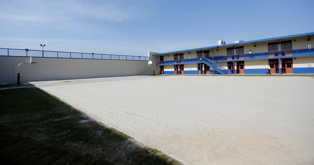 FILE- In this July 31, 2014, file photo shows a sand-covered play area sits in the middle of the Karnes County Residential Center in Karnes City, Texas. (AP Photo/Eric Gay, File)