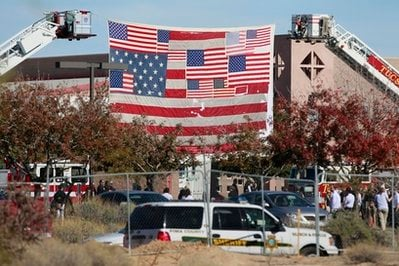 The large American flag recovered from ground zero after the 9/11 attacks hangs from fire truck ladders outside St. Elizabeth Ann Seton Catholic Church in Tucson, Ariz., where funeral services are being held for Christina Taylor Green.