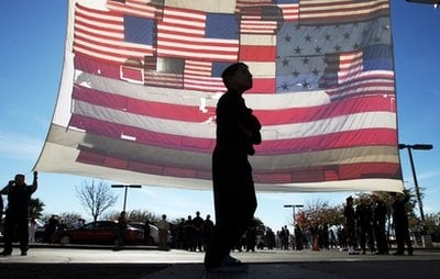 A boy walks past a large American flag recovered from ground zero after the 9/11 attacks, outside the entrance at the St. Elizabeth Ann Seton Church for the funeral of 9-year-old Christina Taylor Green Thursday, Jan. 13, 2011, in Tucson, Ariz.