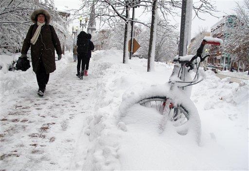 Pedestrians walk through the snow piled streets near Harvard Square Wednesday, Jan. 12, 2011 in Cambridge, Mass. (AP Photo/Kiichiro Sato)