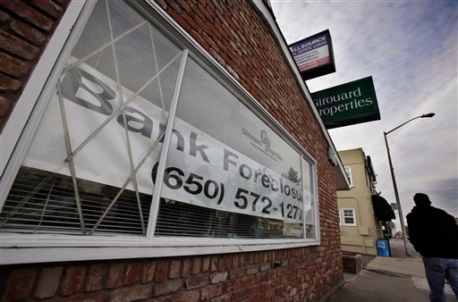 In this Jan. 10 2011 photo, a man walks past the office of Girouard Properties, which specializes in residential re-sale of single family homes and condominiums/townhomes, in San Mateo, Calif. (AP Photo/Paul Sakuma)