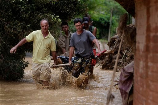 Residents carry a landslide victim in Teresopolis, Rio de Janeiro state, Brazil, Thursday Jan. 13, 2011. At least 350 people have died after landslides hit early Wednesday, and 50 or more were still missing, according to officials. (AP Photo/Felipe Dana)