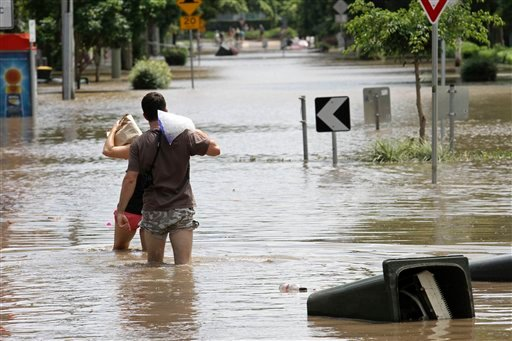 Local residents walk through floodwater after getting ice and food to take to their flooded residence in the suburb of New Farm in Brisbane, Australia, Thursday, Jan. 13, 2011.