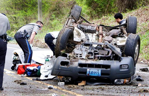 In this May 9, 2017 photo, medics pull a victim from an over turned vehicle in Woodbury, Conn.