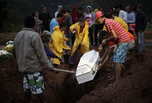 Men lower the casket of Mauro Viana, 9, who died in a landslide in Teresopolis, Rio de Janeiro state, Brazil, Thursday Jan. 13, 2011. (AP Photo/Felipe Dana)