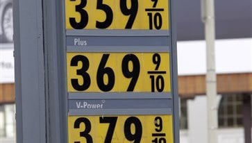 In a Dec. 6, 2010 file photo, a man with a Santa cap looks up at a marquee with high gas prices at a Shell gas station in San Francisco. (AP Photo/Paul Sakuma, File)