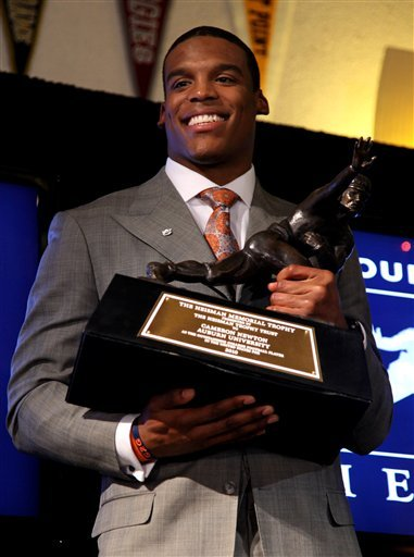In this Dec. 11, 2011, file photo, Auburn quarterback Cam Newton holds the trophy during a news conference after winning the Heisman award, in New York.