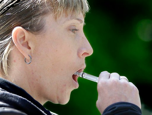 California Highway Patrol Sgt. Jaimi Kenyon, swabs the inside of her mouth to collect saliva during a demonstration of drug testing device Wednesday, May 10, 2017, in Sacramento, Calif.  (AP Photo/Rich Pedroncelli)