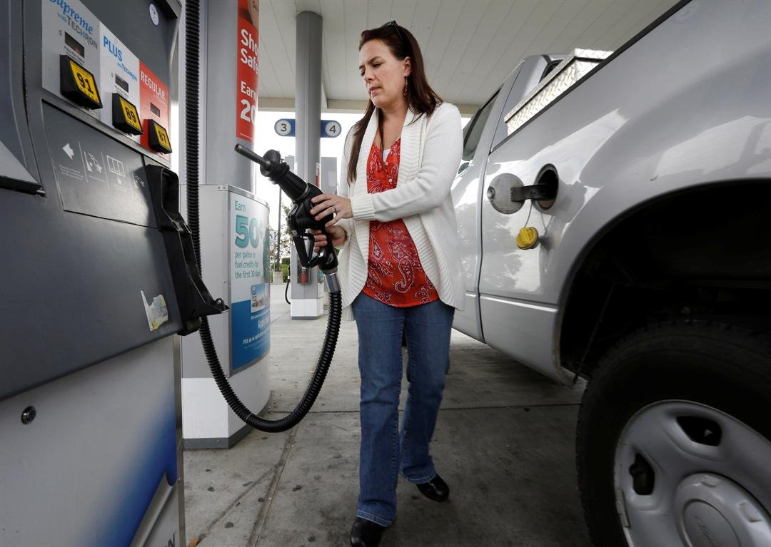 FILE - In this Nov. 12, 2014 file photo, Lydia Holland replaces the gas nozzle after filling up at a gas station in Sacramento, Calif.  (AP Photo/Rich Pedroncelli, File)