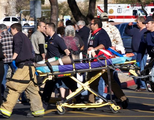 In this Jan. 8, 2011 file photo, emergency personnel move Rep. Gabrielle Giffords, D-Ariz., after she was shot in the head outside a shopping center in Tucson, Ariz. (AP Photo/James Palka, File)
