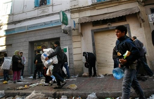 People take food and other goods from a destroyed store in Tunis, Saturday, Jan. 15. 2011.(AP Photo/Christophe Ena)