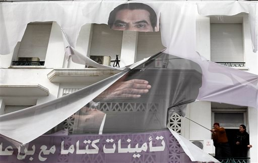 Two men try to remove a torn photo of former Tunisian President Zine El Abidine Ben Ali in the center of Tunis, Sunday, Jan. 16. 2011.