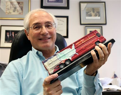 In this March 23, 2010, file photo Sal Russo, the California-based co-founder of the Tea Party Express, holds a model of the Tea Party Express bus in his Sacramento, Calif., office.  (AP Photo/Rich Pedroncelli, File)