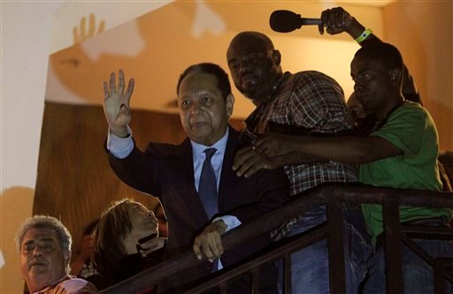 "Former Haitian dictator Jean-Claude ""Baby Doc"" Duvalier, center, waves to supporters from a hotel balcony after his arrival in Port-au-Prince, Haiti, Sunday, Jan. 16, 2011. (AP Photo/Dieu Nalio Chery)"