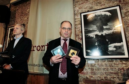 Rudolf Elmer, center, poses for the photographers with digital disks, he claims have information and documents before handing them to WikiLeaks founder Julian Assange, left, during a news conference at the Frontline Club in London, Monday Jan. 17, 2011.