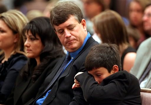In this Jan. 13, 2011 file photo, Dallas Green, right, wipes away a tear while seated next to his father John Green and mother Roxanna Green during the funeral for his sister, 9-year-old Christina Taylor Green, in Tucson, Ariz.