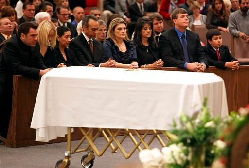 Family, including mother Roxanna Green, third from right, father John Green, second from right, and son Dallas Green, right, kneel in prayer behind the casket during the funeral of his daughter, 9-year-old Christina Taylor Green, Thursday, Jan. 13, 2011.