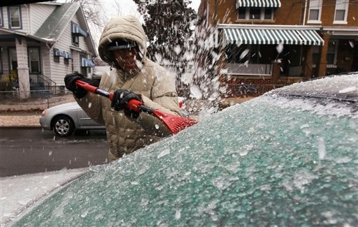 Yvette Judge works to clear the ice from the back window of her car, in Washington, Tuesday, Jan. 18, 2011, after a mix of freezing rain and sleet fell overnight in the Washington area. (AP Photo/Alex Brandon)
