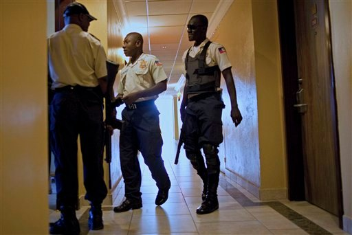 "National police officers patrol a corridor at the hotel's floor where Haiti's former dictator Jean-Claude ""Baby Doc"" Duvalier is staying in Port-au-Prince, Haiti, Tuesday Jan. 18, 2011. (AP Photo/Ramon Espinosa)"