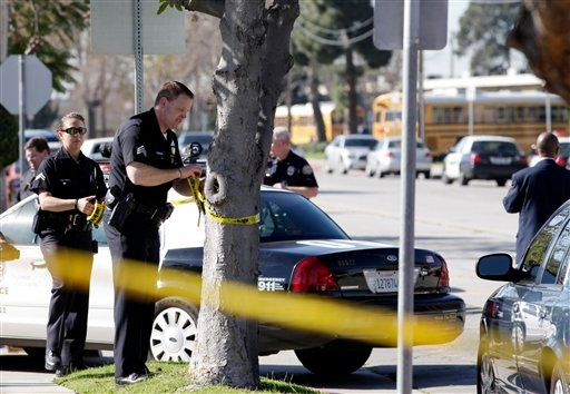Police officers put yellow tape outside Gardena High School in Gardena, Calif., Tuesday, Jan. 18, 2011. A gun in a 10th-grader's backpack accidentally discharged when he dropped the bag, wounding two students at the school, the campus principal said.