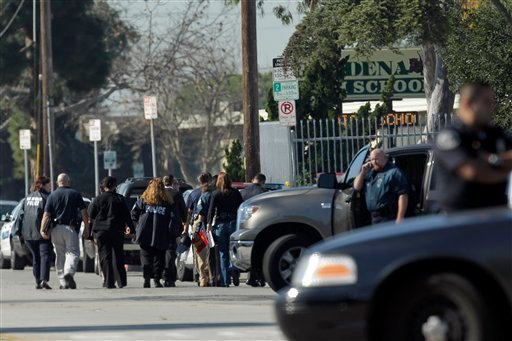 Investigators arrive at Gardena High School in Gardena, Calif., Tuesday, Jan. 18, 2011, after reports of a number of students being wounded during a shooting.