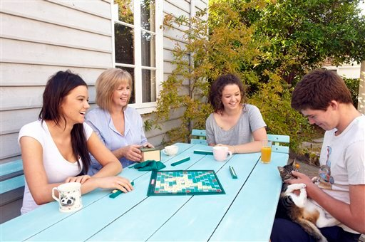 This undated photo courtesy of Frances Andrijich shows Susan Maushart, second from left, with her children, from left to right, Anni, Sussy and Bill (with cat Hazel) as they play a board game together.
