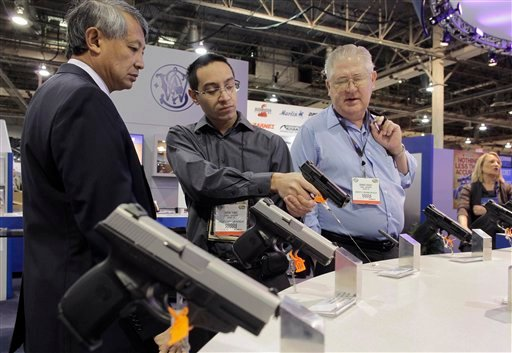 Domestic firearms retailers examine a Smith & Wesson hand gun at the Shooting, Hunting and Outdoor Trade show, Tuesday, Jan. 18, 2011 in Las Vegas.