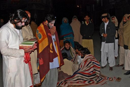 Two Pakistanis, left, read verses of the Quran while gathering with others outside their homes as a severe earthquake hits the area in Quetta, Pakistan, early Wednesday, Jan. 19, 2011.