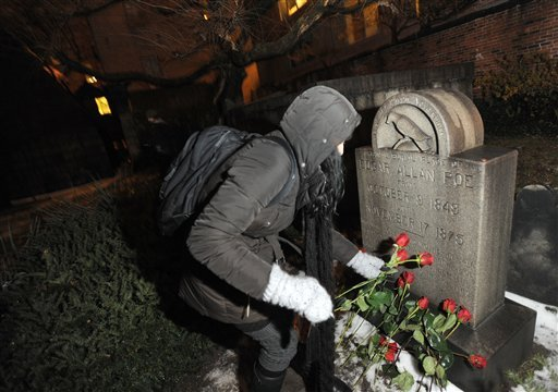 Edgar Allan Poe fan Cynthia Pelayo of Chicago lays roses near the author's original burial place Jan. 19, 2011 at Westminster Church and Cemetary in Baltimore. (AP Photo/Steve Ruark)