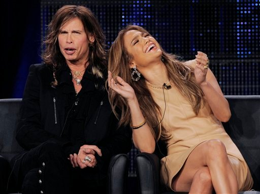 """Steven Tyler, left, and Jennifer Lopez, new judges on the FOX series """"American Idol,"""" react during a panel discussion on the show at the FOX Broadcasting Company Television Critics Association winter press tour in Pasadena, Calif., Tuesday, Jan. 11, 2011."""