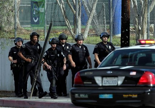 A group of police officers search outside El Camino Real High School in the Woodland Hills section of Los Angeles Jan. 19, 2011. A school police officer was shot near the high school but his bulletproof vest took the hit Wednesday. (AP Photo/Jae C. Hong)