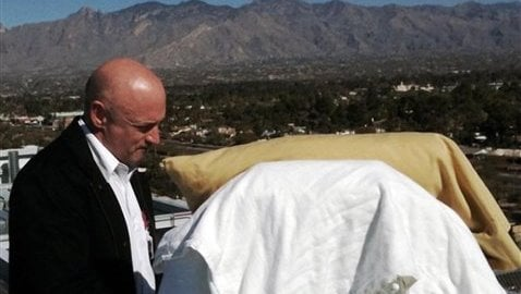 In this photo provided by the office of U.S. Rep Gabrielle Giffords, Giffords' husband, Mark Kelly, stands with his wife as she looks from her bed at the Santa Catalina Mountains.  (AP Photo/Office of U.S. Rep. Gabrielle Giffords)