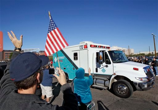 People wave and applaud as the ambulance carrying U.S. Rep. Gabrielle Giffords, D-Ariz., leaves University Medical Center, Friday, Jan. 21, 2011, in Tucson, Ariz. Giffords is being transported to a medical facility in Houston.