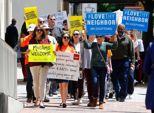 Protesters hold signs and march outside the US 4th Circuit Court of Appeals in Richmond, Va., Monday, May 8, 2017. (AP Photo/Steve Helber)
