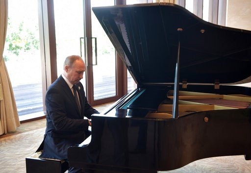 Russian President Vladimir Putin plays piano before his talks with Chinese President Xi Jinping prior to the opening ceremony of the Belt and Road Forum in Beijing, Sunday, May 14, 2017.