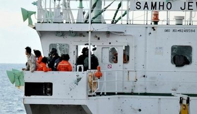 In this photo released by the Arabian Navy via Yonhap, members of South Korean naval special forces rescue crew members from Somali pirates aboard the South Korean cargo ship Samho Jewelry in the Arabian Sea, Friday, Jan. 21, 2011.