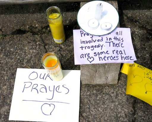 Well-wishing messages and candles for an injured employee are shown outside a grocery store in Estacada, Ore., Monday, May 15, 2017. Police say a man carrying what appeared to be a human head stabbed an employee at the grocery store. (AP Photo/Gillian Fla