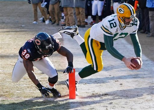 Green Bay Packers quarterback Aaron Rodgers (12) scores a touchdown past Chicago Bears safety Danieal Manning (38) during the first half of the NFC Championship NFL football game Sunday, Jan. 23, 2011, in Chicago. (AP Photo/Charles Rex Arbogast)