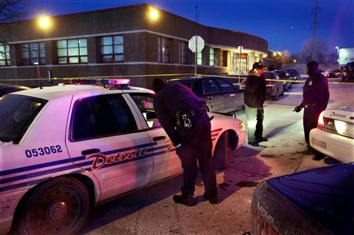 Detroit police stand outside the precinct 6 building in northwest Detroit where a gunman walked into the police station and opened fire injuring three police officers, Sunday, Jan. 23, 2011. (AP Photo/Carlos Osorio)