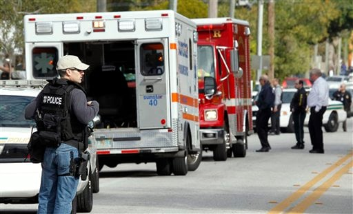 An armed police officer stands near rescue vehicles about a block away from where a U.S. Marshal and two St. Petersburg police officers were shot while trying to serve an arrest warrant Jan. 24, 2011 in south St. Petersburg, Fla. (AP Photo/Chris O'Meara)