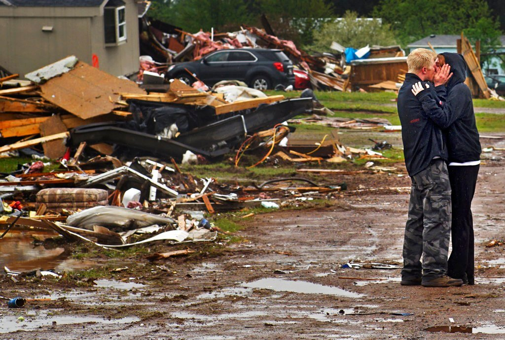 Ron Bloomberg, who witnessed victim and neighbor Eric Gavin's body being recovered, embraces his girlfriend as he returns to his home in Chetek, Wis., after a tornado flattened a trailer park and nearby trees. (Richard Tsong-Taatarii/Star Tribune via AP)