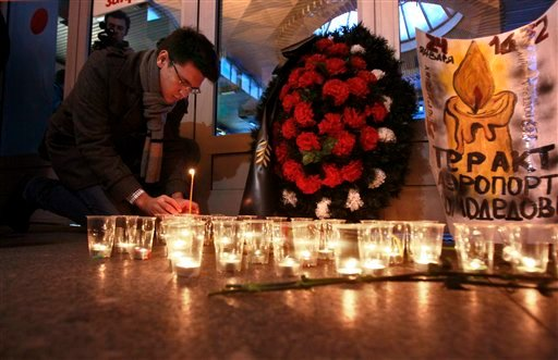 A man lights a candle at the Moskovsky railway station in St.Petersburg, Russia, Tuesday, Jan. 25, 2011, to commemorate the victims of a suicide bombing at Moscow's Domodedovo airport.
